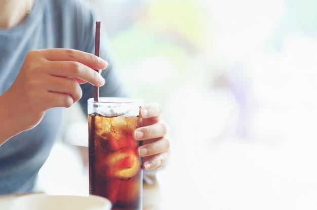 Nahaufnahmefrau hand, die glas cola hält, trinken im restauranthintergrund, frauenhandglas