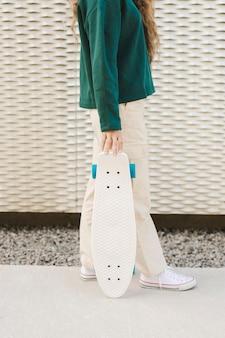 Nahaufnahmefrau im freien mit skateboard