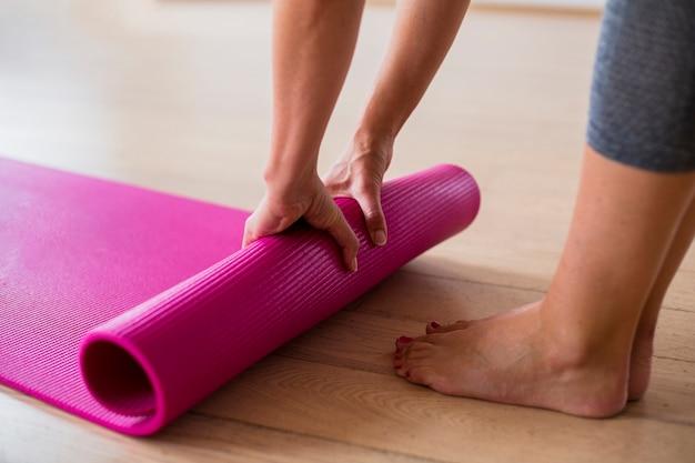 Nahaufnahmefrau in der sportkleidung, die yogamatte einstellt