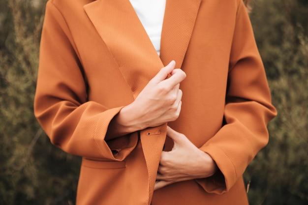 Nahaufnahmefrau in einem trenchcoat
