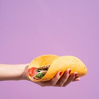 Nahaufnahmefrau mit burrito und purpurrotem hintergrund