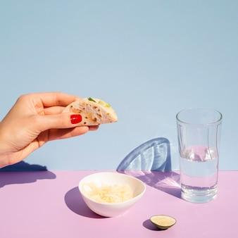 Nahaufnahmefrau mit dem glas wasser kleinen taco halten