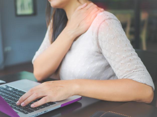 Nahaufnahmefrau mit den händen, die ihre schulterschmerzen halten. büro-syndrom