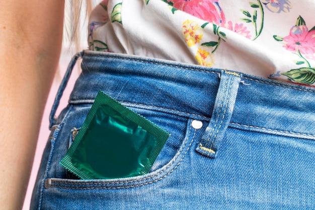 Nahaufnahmefrau mit eingewickeltem kondom in ihrer tasche
