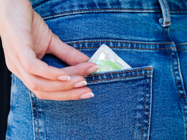 Nahaufnahmefrau mit grünem kondom in der gesäßtasche