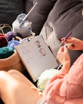 Nahaufnahmefrau mit häkelnden zeichnungen