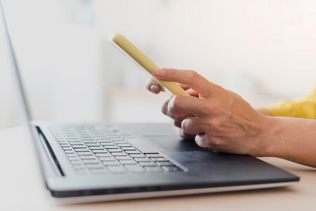 Nahaufnahmefrau mit laptop und smartphone