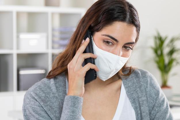 Nahaufnahmefrau mit maske, die am telefon spricht