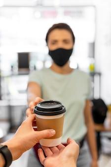Nahaufnahmefrau mit maske, die kaffee kauft