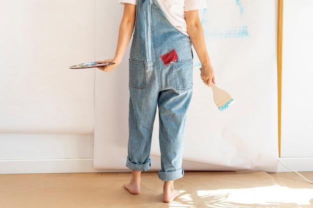 Nahaufnahmefrau mit paletten- und bürstenrückseitenansicht