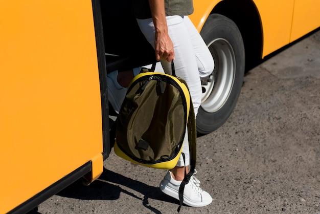 Nahaufnahmefrau mit rucksack, der aus bus aussteigt