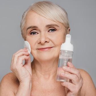 Nahaufnahmefrau mit serum und wattepad