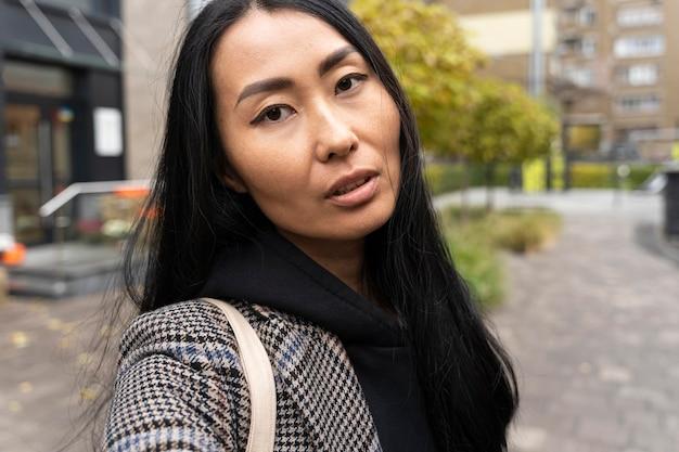 Nahaufnahmefrau mit städtischem hintergrund