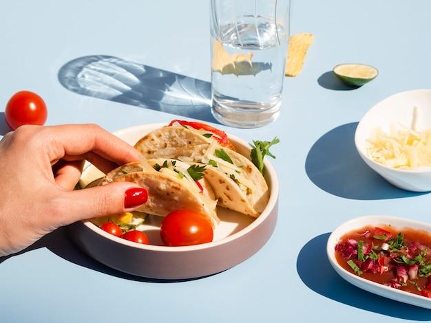 Nahaufnahmefrau mit taco und köstlicher soße