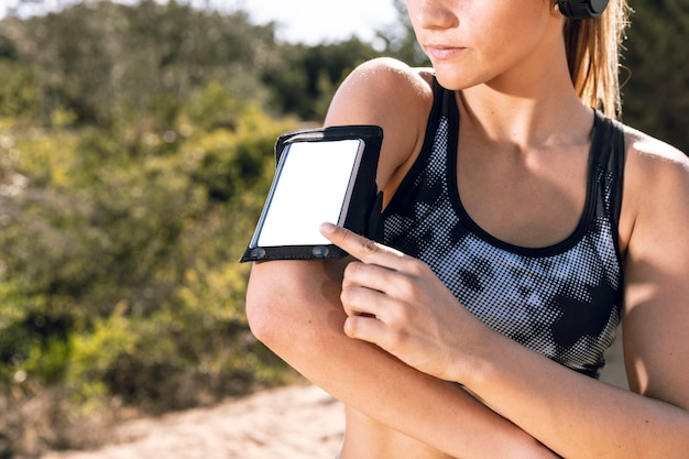 Nahaufnahmefrau mit telefonarmbandmodell