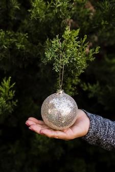 Nahaufnahmefrau mit weihnachtsbaum und kugel