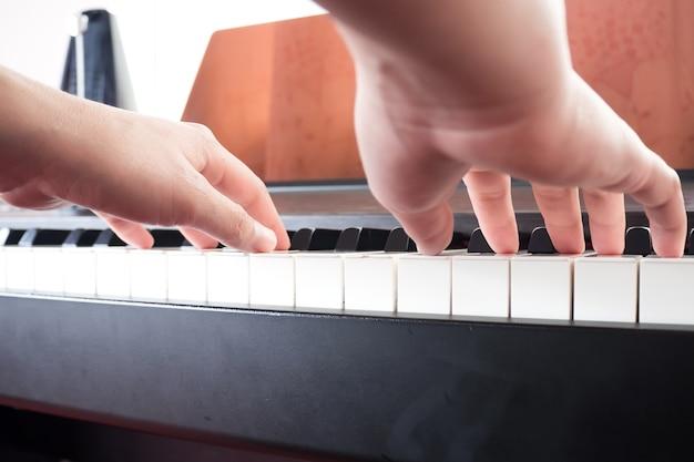 Nahaufnahmefrau übergibt das spielen des klaviers. musik und kunst hintergrund.
