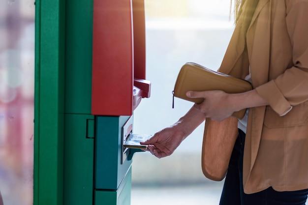 Nahaufnahmefrau, welche die geldbörse hält und das bargeld über atm, geschäfts-automatische erzähler-maschine zurücknimmt