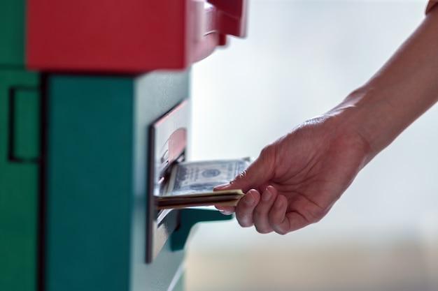 Nahaufnahmefrau, welche die geldbörse hält und das bargeld über atm herausnimmt
