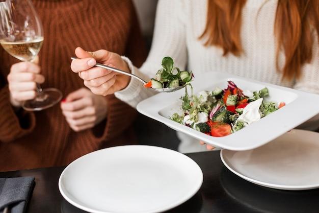 Nahaufnahmefrauen, die wein und salat haben