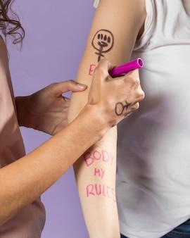 Nahaufnahmefrauen-malereifreundarm für protest