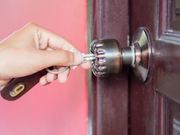 Nahaufnahmefrauen öffnet die braune holztür, indem sie den schlüssel dreht