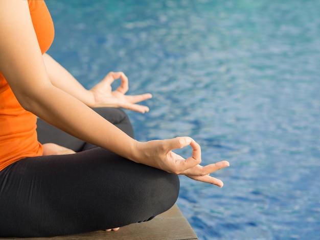 Nahaufnahmefrauen-trainingsyoga und -meditation am poolside