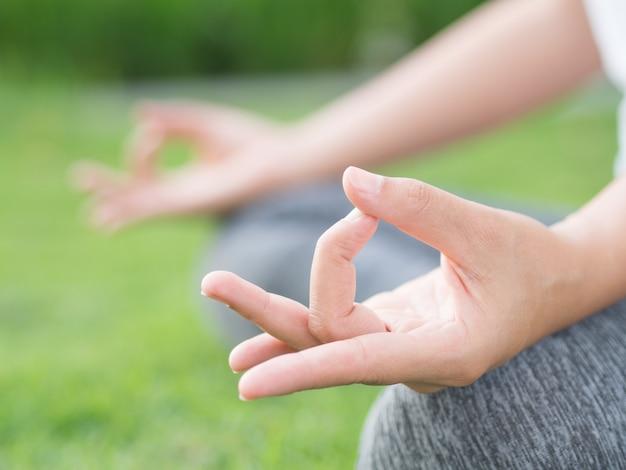 Nahaufnahmefrauen-yogafinger, der auf händen im weichzeichnungshintergrund fungiert.