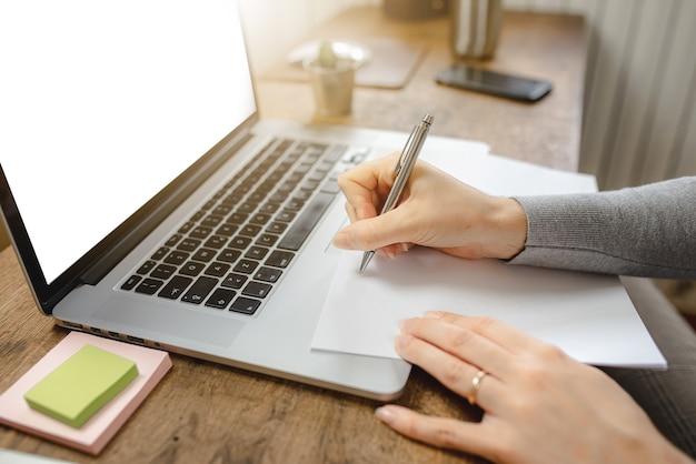 Nahaufnahmefrauenhände, die am laptop arbeiten und notizen in einem papier machen. schreibtisch am arbeitsplatz.