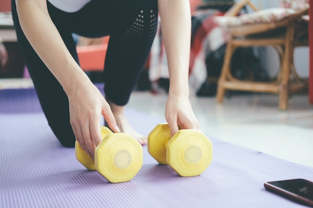 Nahaufnahmefrauenhände, die hantel halten. konzept eines gesunden lebensstils und fitness.