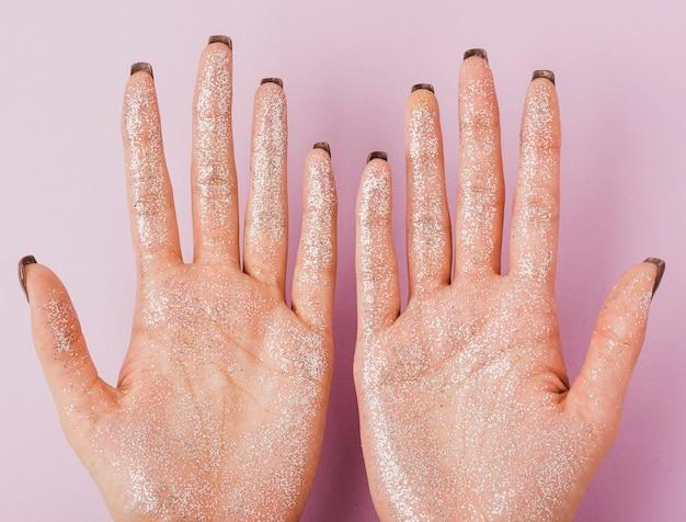 Nahaufnahmefrauenhände mit draufsicht des silbernen funkelns