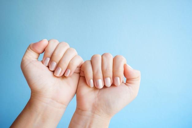 Nahaufnahmefrauenhände mit einem schönen maniküreisolat auf blauem hintergrund.