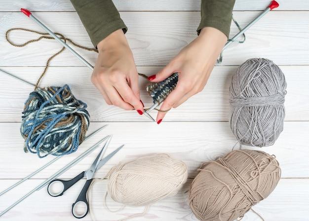 Nahaufnahmefrauenhände stricken aus bunten fäden winterkleidung