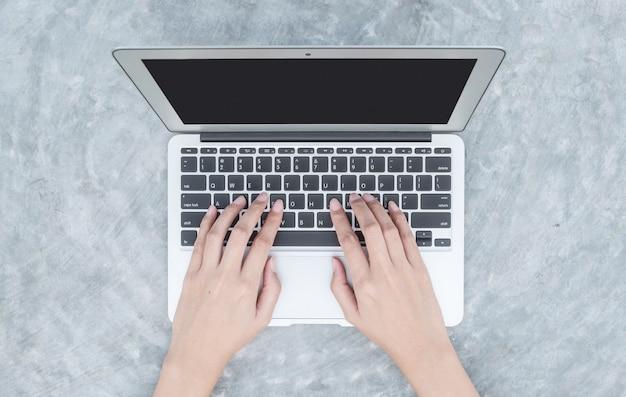 Nahaufnahmefrauenhand, die auf tastatur am notebook schreibt