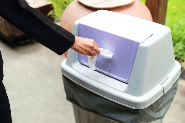 Nahaufnahmefrauenhand, die blatt papier im abfall wirft