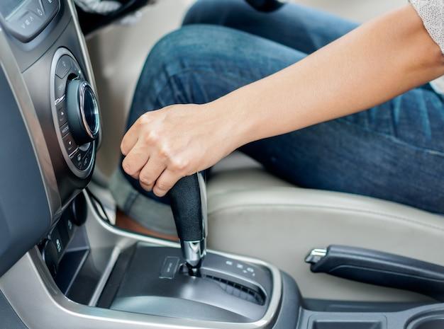 Nahaufnahmefrauenhand, die den schalthebel verschiebt und ein auto fährt