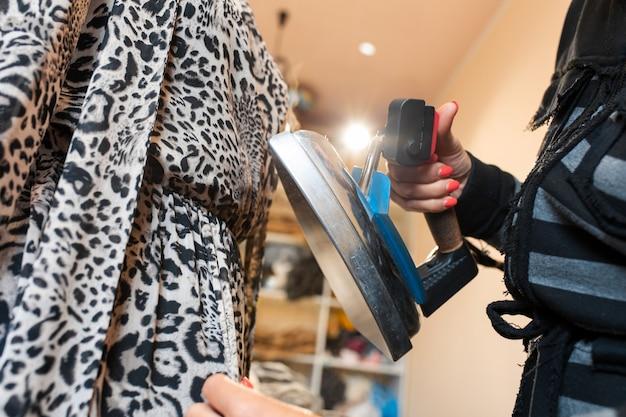 Nahaufnahmefrauenhand macht das kleid mit einem dampfbügeleisen auf einem mannequin glatt