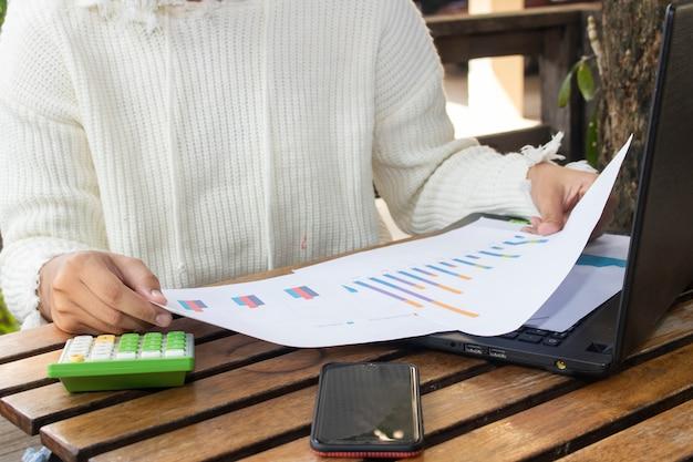 Nahaufnahmefrauenhand mit papierdiagramm, unter verwendung des computer notizbuchlaptops und des smartphone