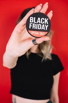 Nahaufnahmefrauenhand mit schwarzem freitag-zeichen