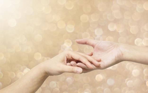 Nahaufnahmefrauenhandgriff eine andere frauenhand auf abstraktem hintergrund des braunen lichtes