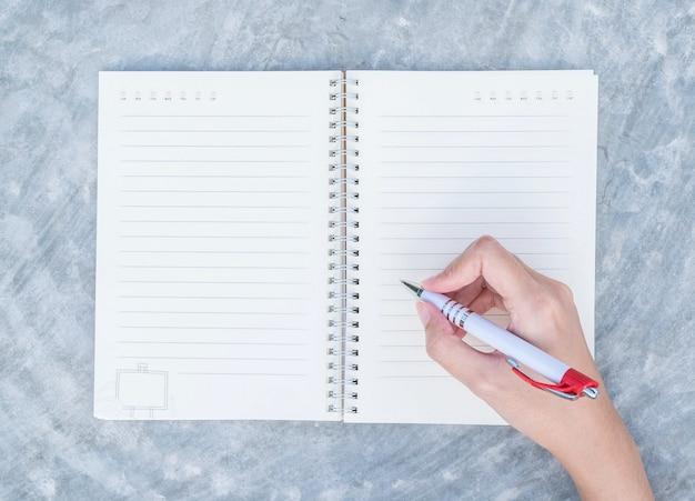 Nahaufnahmefrauenhandschrift auf anmerkungsbuch auf konkretem schreibtisch in draufsicht maserte hintergrund unter tageslicht im garten