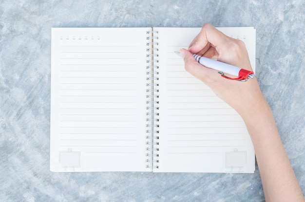Nahaufnahmefrauenhandschrift auf anmerkungsbuch in der draufsicht