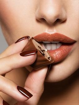 Nahaufnahmefrauenmund mit brauner süßigkeit nahe lippen.