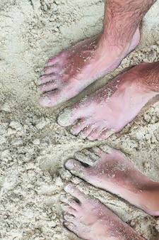 Nahaufnahmefüße eines jungen paares auf weißem sandstrand