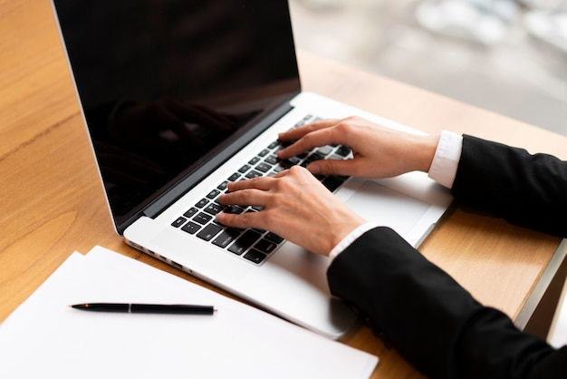 Nahaufnahmegeschäftsmann, der an einem laptop arbeitet