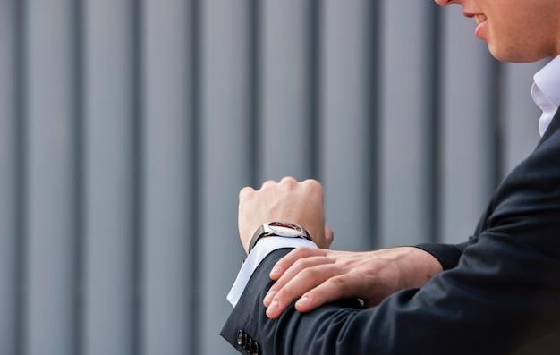 Nahaufnahmegeschäftsmann, der armbanduhr betrachtet