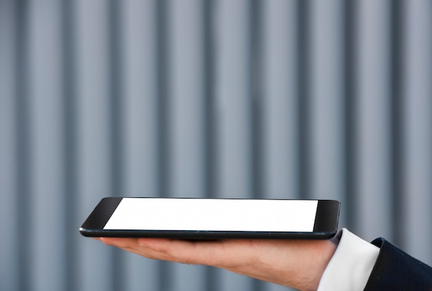 Nahaufnahmegeschäftsmann, der in der hand tablette hält