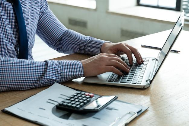 Nahaufnahmegeschäftsmann, der rechner und laptop für die berechnung der finanzsteuerforschung verwendet