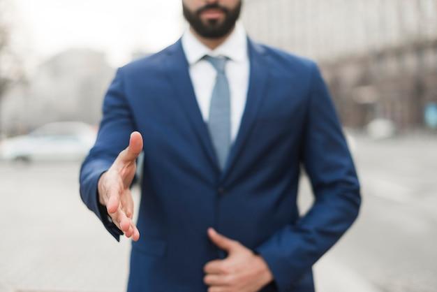 Nahaufnahmegeschäftsmann mit hand bereit zum schütteln