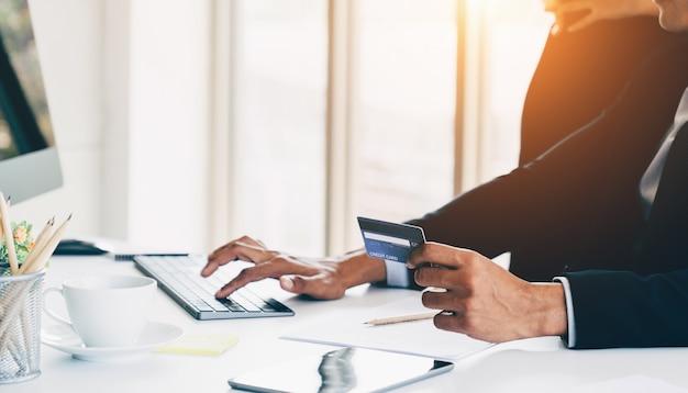 Nahaufnahmegeschäftsmann übergibt das halten unter verwendung der kreditkarte für online-banking im büro